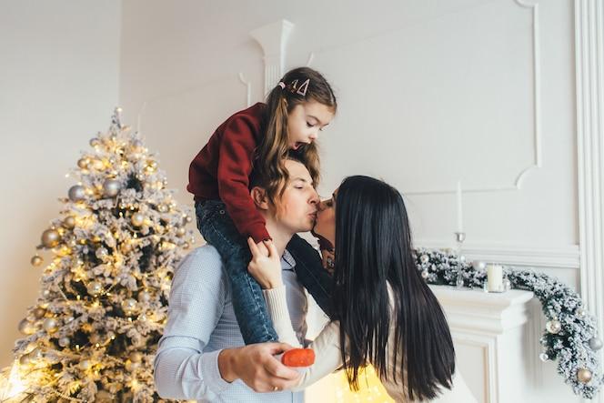 Joven familia posa delante de un brillante árbol de navidad en una acogedora habitación de lujo