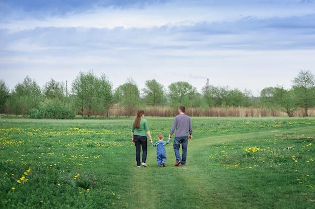 Joven familia y su hijo caminan en un prado de primavera