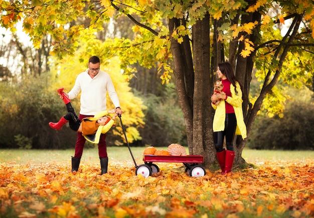 Joven familia de tres con pequeño perro divirtiéndose en el parque otoño.
