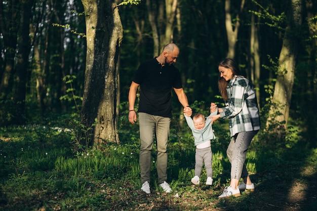 Joven fanily con pequeña hija en el bosque