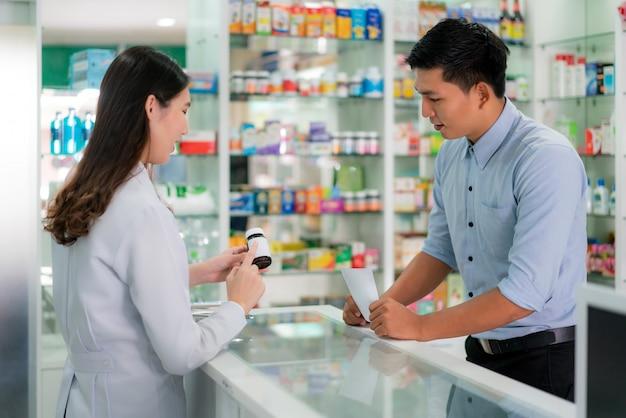 Joven farmacéutica asiática con una encantadora sonrisa amable y explicando la medicina a su cliente en la farmacia.