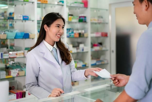 Joven farmacéutica asiática con una sonrisa encantadora y amable y recibe medicamentos recetados por el hombre.