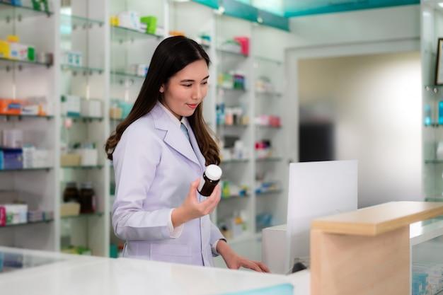Joven farmacéutica asiática con sonrisa sosteniendo una botella de medicina y buscando ese producto en la computadora