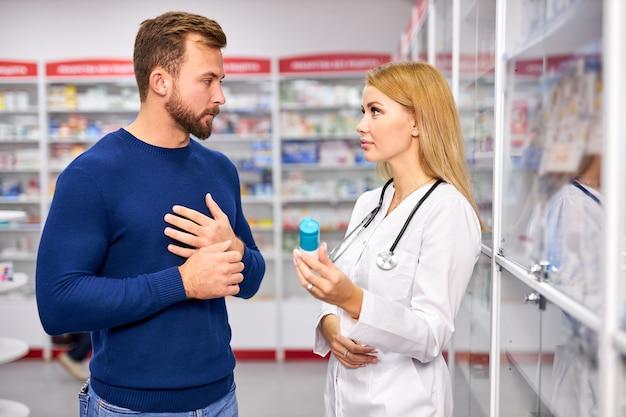 Joven farmacéutico femenino útil caucásico tratando con un cliente masculino