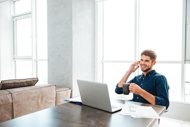 Joven feliz bebiendo té y sentado junto a la mesa con ordenador portátil y documentos mientras habla en su teléfono. mirando portátil