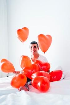 Joven feliz en la cama entre globos en forma de corazones