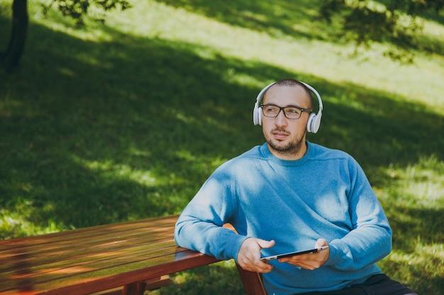 Joven feliz, empresario o estudiante con gafas de camisa azul casual sentado en la mesa con auriculares, tablet pc en el parque de la ciudad, escuchar música, descansar al aire libre en la naturaleza verde. concepto de ocio de estilo de vida.