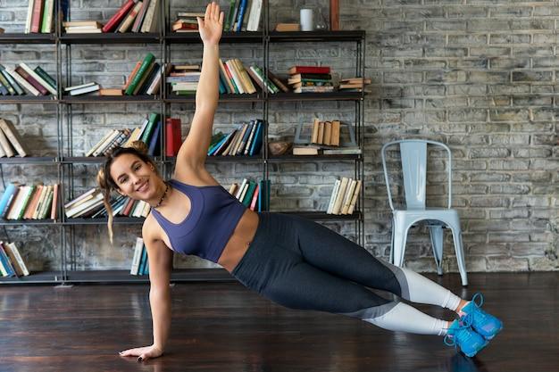 Joven feliz fitness mujer haciendo ejercicio tablón lateral durante el yoga en casa