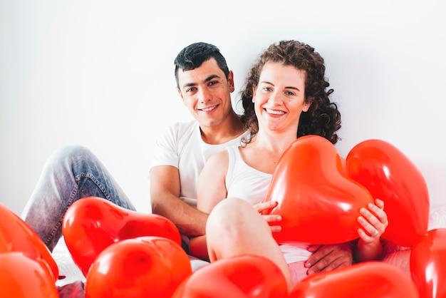 Joven feliz hombre y mujer entre globos en forma de corazones