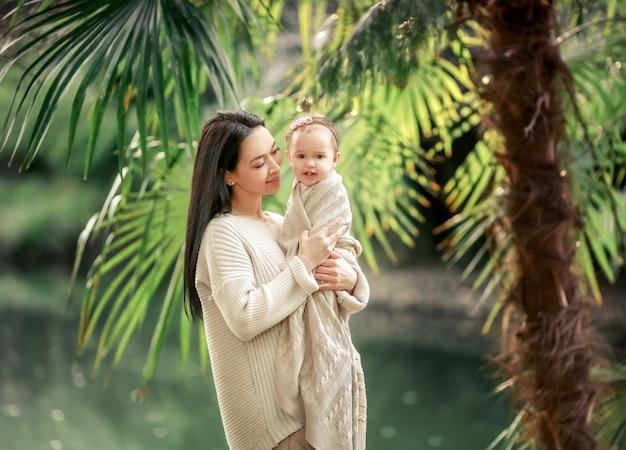 Joven y feliz madre cuida a su pequeño hijo y camina por la orilla del lago en el verano en el parque