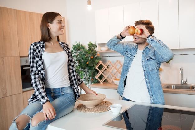 Joven feliz y mujer en la cocina, desayuno, pareja divirtiéndose juntos en la mañana, sonriendo, sosteniendo la manzana, divertido, loco, riendo