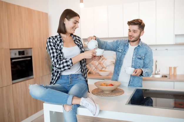 Joven feliz y mujer en la cocina, desayuno, pareja juntos en la mañana, sonriendo, tomando té