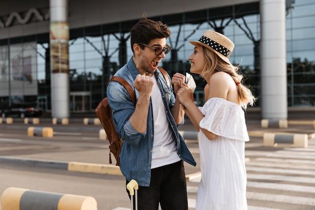 Joven feliz y mujer tienen boletos y se regocijan