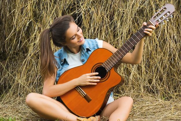 Joven y feliz mujer tocando la guitarra en el pueblo