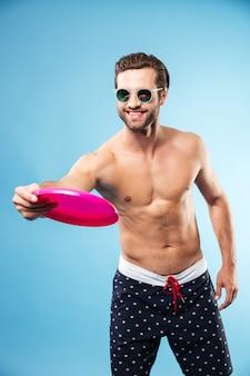 Joven feliz en pantalones cortos de verano jugando frisbee juego
