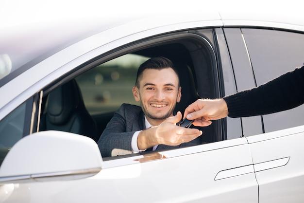 Joven feliz recibiendo las llaves del coche de su nuevo automóvil