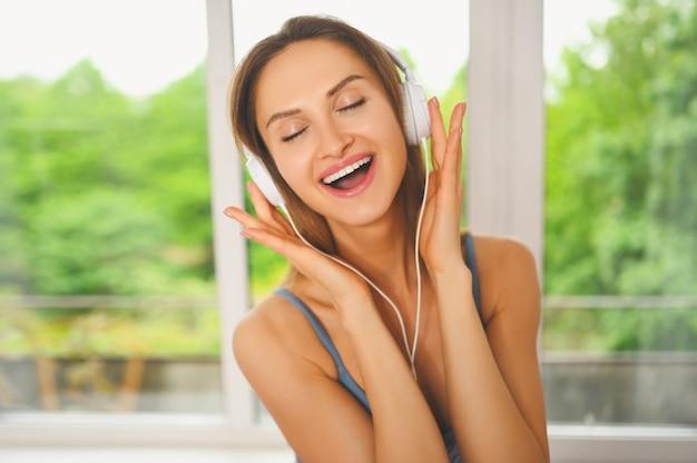 Joven feliz sonriendo hermosa mujer slim fit en ropa deportiva azul escuchando música en grandes auriculares blancos en casa