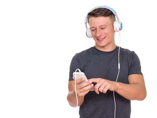 Joven feliz con teléfono móvil y auriculares