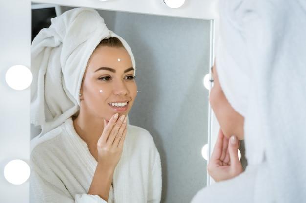 Una joven feliz con una toalla frente a un espejo aplica crema en la cara, un concepto de cuidado de la piel en el hogar
