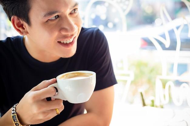 El joven está feliz de tomar café.