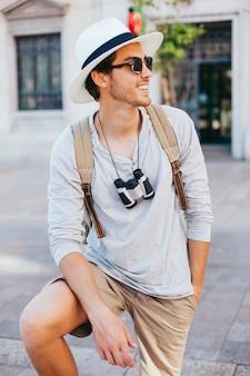 Joven y feliz turista posando con gafas de sol