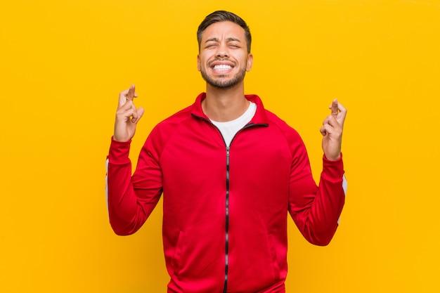 Joven filipino fitness hombre cruzando los dedos para tener suerte