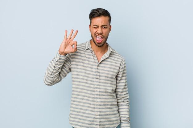 Joven filipino guapo guiña un ojo y tiene un gesto bien con la mano.