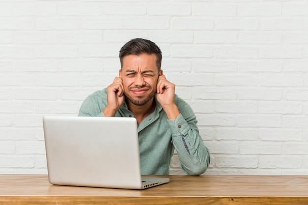 Joven filipino hombre sentado trabajando con su computadora portátil cubriendo las orejas con las manos.