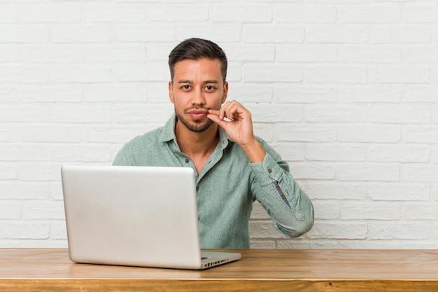 Joven filipino hombre sentado trabajando con su computadora portátil con los dedos en los labios, manteniendo el secreto.