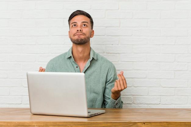 Joven filipino hombre sentado trabajando con su computadora portátil que muestra que ella no tiene dinero.