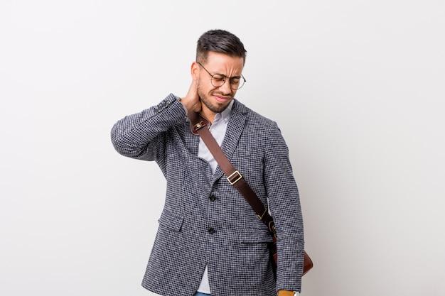 Joven filipino de negocios contra una pared blanca que sufre dolor de cuello debido a un estilo de vida sedentario.
