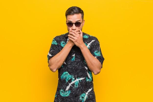 Joven filipino con ropa de verano sorprendido cubriendo la boca con las manos.