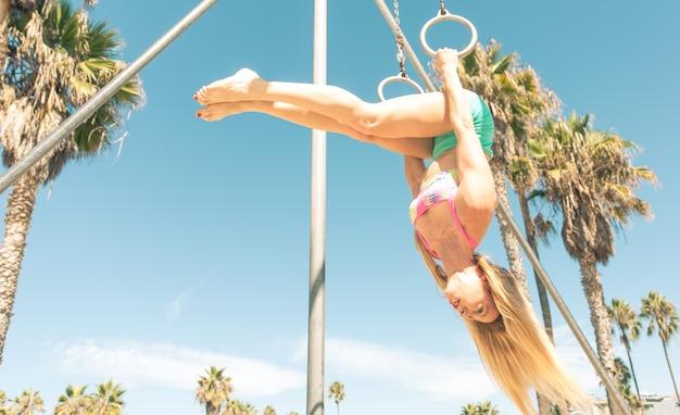 Joven fitness mujer haciendo ejercicio en la playa
