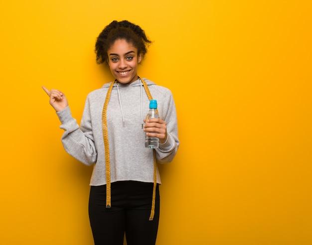 Joven fitness mujer negra apuntando hacia un lado con el dedo sosteniendo una botella de agua