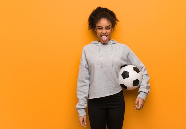 Joven fitness mujer negra divertida y amigable mostrando lengua. sosteniendo un balón de fútbol.