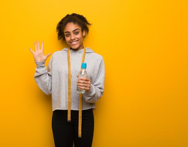 Joven fitness mujer negra mostrando el número cinco. sosteniendo una botella de agua.