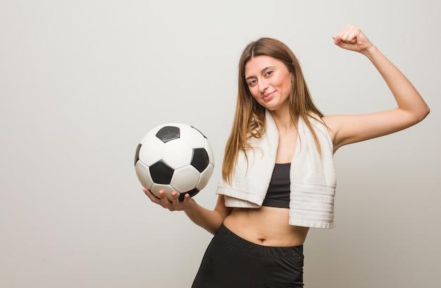 Joven fitness mujer rusa que no se rinde. sosteniendo un balón de fútbol.