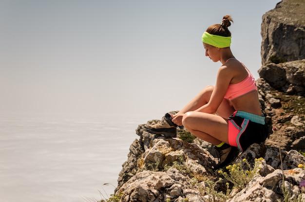 Joven fitness mujer trail runner atar cordones de los zapatos en la cima de la montaña