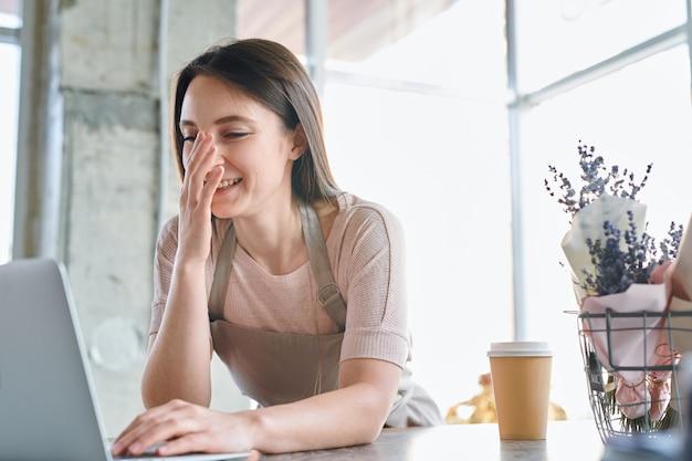Joven florista alegre o ligeramente confundido mirando la pantalla del portátil con la mano en la cara durante el trabajo