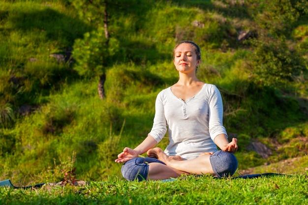 Joven en forma deportiva haciendo yoga lotus pose oudoors