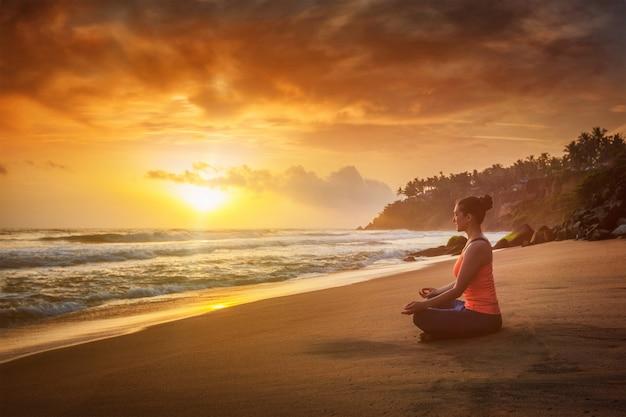 Joven en forma deportiva haciendo yoga oudoors en la playa