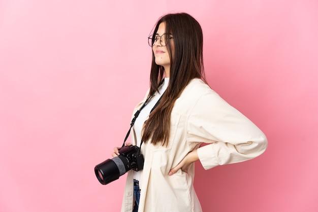 Joven fotógrafa brasileña aislada sobre fondo rosa que sufre de dolor de espalda por haber hecho un esfuerzo