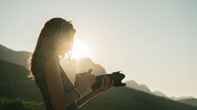 Joven fotógrafa mirando su cámara réflex digital