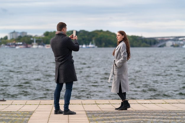 Joven fotografiando a su novia o esposa en un ventoso paseo marítimo en un frío día de otoño usando su teléfono móvil