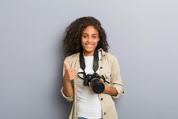 Joven fotógrafo afroamericano mujer sosteniendo una cámara sonriendo y levantando el pulgar