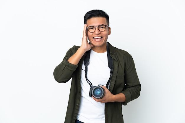 Joven fotógrafo ecuatoriano aislado en la pared blanca gritando con la boca abierta