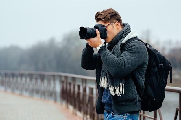 Joven fotógrafo con estilo tiene cámara profesional, tomar fotos.
