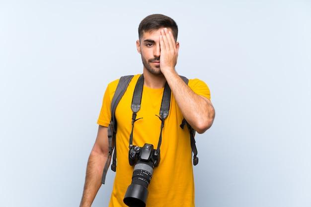 Joven fotógrafo hombre cubriendo un ojo con la mano