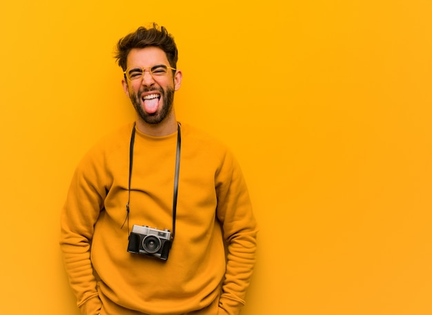 Joven fotógrafo hombre divertido y amigable mostrando lengua
