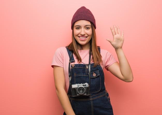Joven fotógrafo lindo mujer mostrando número cinco